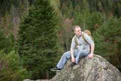 Male climber with brown backpack on the peak of rock Royalty Free Stock Photography