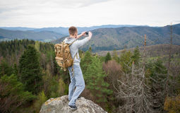 Male climber with brown backpack on the peak of rock Stock Photo