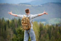 Male climber with brown backpack on the peak of rock Stock Image