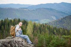 Male climber with brown backpack on the peak of rock Stock Photography