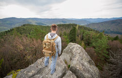 Male climber with brown backpack on the peak of rock. Young male tourist with a backpack standing on the edge of a rock and looking into the distance on the Stock Images