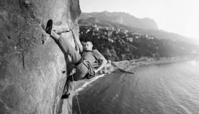 Male climber climbing big boulder in nature with rope Stock Photos