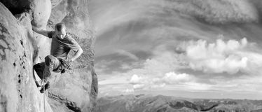 Male climber climbing big boulder in nature with rope Stock Image