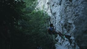 Male climber down the rope. Along the cliff stock video
