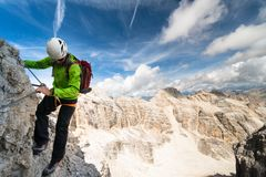 Male climber on an exposed Via Ferrata in the Dolomites. Male climber on a steep and exposed Via Ferrata in the South Tyrol in the Italian Dolomites with a Stock Photo