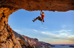 Male climber gripping on handhold while climbing in cave. Royalty Free Stock Images