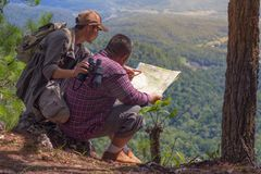 Male climber looking at the map and relaxing on the mountain. - royalty free stock images
