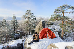 Male climber nearly his tent on the top of rock Stock Image