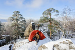 Male climber nearly his tent on the top of rock Royalty Free Stock Photo