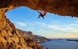 Male climber on overhanging rock against beautiful view of coast Royalty Free Stock Photo