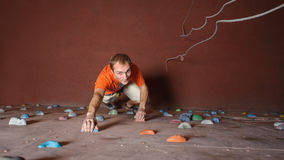 Male climber practicing rock-climbing on a rock wall indoors stock photo