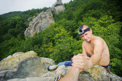 Male climber is reaching for a helping-hand from his partner. Young shirtless male climber is reaching for a helping-hand from his partner at the top of his Stock Image