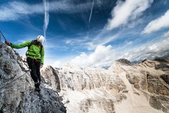 Male climber on a steep and exposed Via Ferrata. In the Italian Dolomites with a fantastic background panorama Royalty Free Stock Image