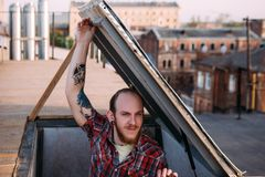 Male climbing on roof. Creative leisure time Royalty Free Stock Photo