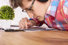 Male closely looking at tablet. Closeup of caucasian male with headphones on, very closely looking at tablet, placed on wooden table with small plant Stock Image