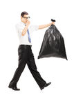 Male closing his nose and carrying a stinky garbage bag. Full length portrait of a male closing his nose and carrying a stinky garbage bag isolated on white stock images