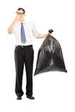 Male closing his nose and holding a stinky garbage bag. Full length portrait of a male closing his nose and holding a stinky garbage bag isolated on white Royalty Free Stock Photography
