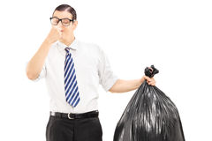 Male closing his nose and holding a stinky garbage bag. Isolated on white background Stock Photos