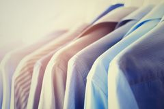 Male clothes, jackets and shirts hanging on clothes rail. Blue color clothes. Copy space. Image with toned effect.  Stock Image