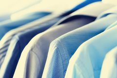 Male clothes, jackets and shirts hanging on clothes rail. Blue color clothes. Copy space. Image with toned effect.  Royalty Free Stock Image