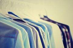 Male clothes, jackets and shirts hanging on clothes rail. Blue color clothes. Copy space. Image with toned effect.  Stock Images