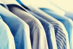Male clothes, jackets and shirts hanging on clothes rail. Blue color clothes. Copy space. Image with toned effect.  Stock Photos