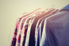 Male clothes, jackets and shirts hanging on clothes rail. Blue color clothes. Copy space. Image with toned effect.  Royalty Free Stock Photos
