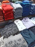 Male cloths of different colours on counter in store. royalty free stock images
