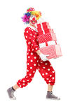 Male clown carrying a pile of presents Royalty Free Stock Image