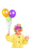 Male clown in costume holding bunch of balloons and popcorn box Royalty Free Stock Photos