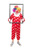Male clown holding a big picture frame Stock Images