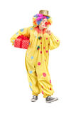 Male clown holding a present Royalty Free Stock Photo
