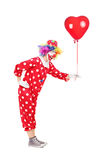 Male clown holding a red balloon Stock Photos