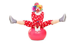 Male clown performing on a pilates ball Stock Image