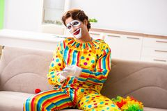 The male clown preparing for perfomance at home. Male clown preparing for perfomance at home royalty free stock photos