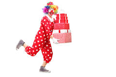Male clown running and holding presents Royalty Free Stock Photos