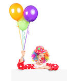 Male clown wqith balloons posing behind panel Stock Image