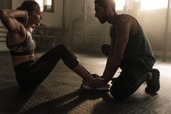 Male coach assisting woman in doing sit-ups at gym. Male coach assisting women in doing sit-ups at gym. Woman working out on her abs with help from male personal Stock Photo