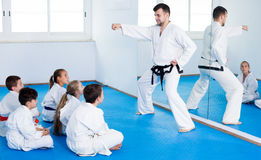 Male coach explaining new maneuvers to children. Cheerful young male coach explaining new maneuvers to children in karate class. Focus on the boy Royalty Free Stock Photos