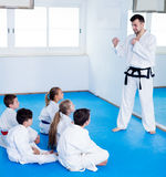 Male coach explaining new maneuvers to children Stock Photography