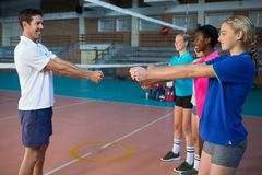 Male coach and female players performing stretching exercise. In court Royalty Free Stock Photography