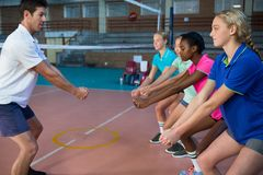 Male coach and female players performing stretching exercise. In court Stock Images