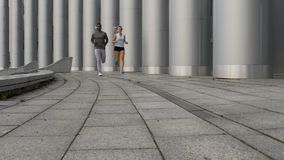 Male coach running together with female trainee, personal workout sessions. Stock footage stock footage