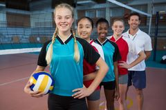 Male coach and volleyball players standing in a row. Portrait of male coach and volleyball players standing in a row royalty free stock photo