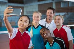Male coach and volleyball players taking selfie. In court Stock Images