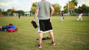 Male coaching kids during practice at Baseball Field stock video