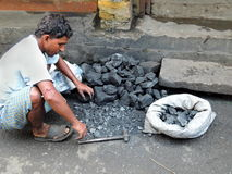 A male coal breaker breaking coal with hammer. Kolkata, India - March 6, 2016: A male worker breaking coal with hammer Stock Image