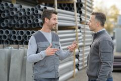 2 male coleagues chatting at pipe factory yard. Coleagues royalty free stock photo