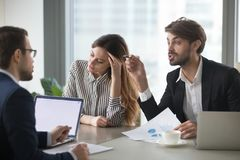 Male colleagues disputing during company business meeting. Male colleagues argue having dispute at company briefing, women worker stay calm and peaceful managing royalty free stock photos
