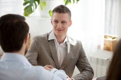 Male colleagues get acquainted handshaking at meeting. Back view of male employee shake hand of colleague during office business meeting, businessmen handshake royalty free stock photography